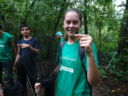Conservation volunteer holds out a finger as a butterfly lands on it during a survey in the forest